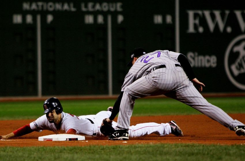 BOSTON - OCTOBER 25: Mike Lowell #25 of the Boston Red Sox slides safely under the tag of Garrett Atkins #27 of the Colorado Rockies during Game Two of the 2007 Major League Baseball World Series at Fenway Park on October 25, 2007 in Boston, Massachusetts. (Photo by Jim McIsaac/Getty Images)