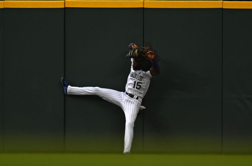 Aug 17, 2019; Denver, CO, USA; Colorado Rockies left fielder Raimel Tapia (15) pulls in a fly ball on the wall in the fourth inning against the Miami Marlins at Coors Field. Mandatory Credit: Ron Chenoy-USA TODAY Sports