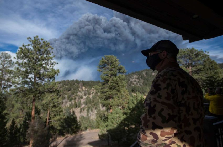 A resident looks out from his porch at the Cameron Peak Fire, the largest wildfire in Colorado history, as it burns outside Estes Park, Colo. on Friday, Oct. 16, 2020. 101620 Cameronpeakfireestespark 20 Bb
