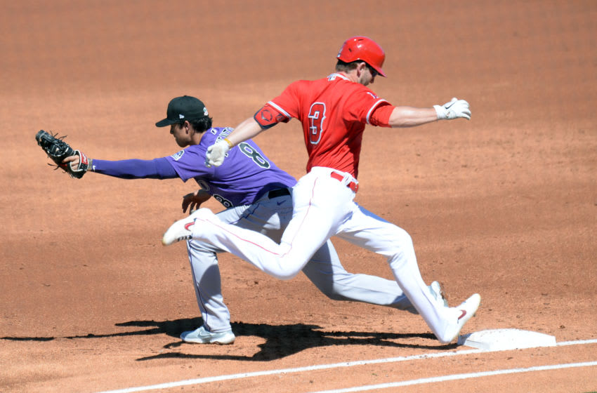 Mar 6, 2021; Tempe, Arizona, USA; Los Angeles Angels third baseman Taylor Ward (3) is forced out at first base by Colorado Rockies first baseman Josh Fuentes (8) during the second inning of a spring training game at Tempe Diablo Stadium. Mandatory Credit: Joe Camporeale-USA TODAY Sports