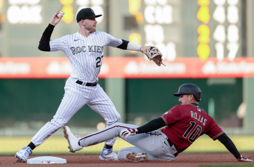 Apr 7, 2021; Denver, Colorado, USA; Colorado Rockies shortstop Trevor Story (27) turns a double play as Arizona Diamondbacks shortstop Josh Rojas (10) slides out into second base in the first inning at Coors Field. Mandatory Credit: Isaiah J. Downing-USA TODAY Sports