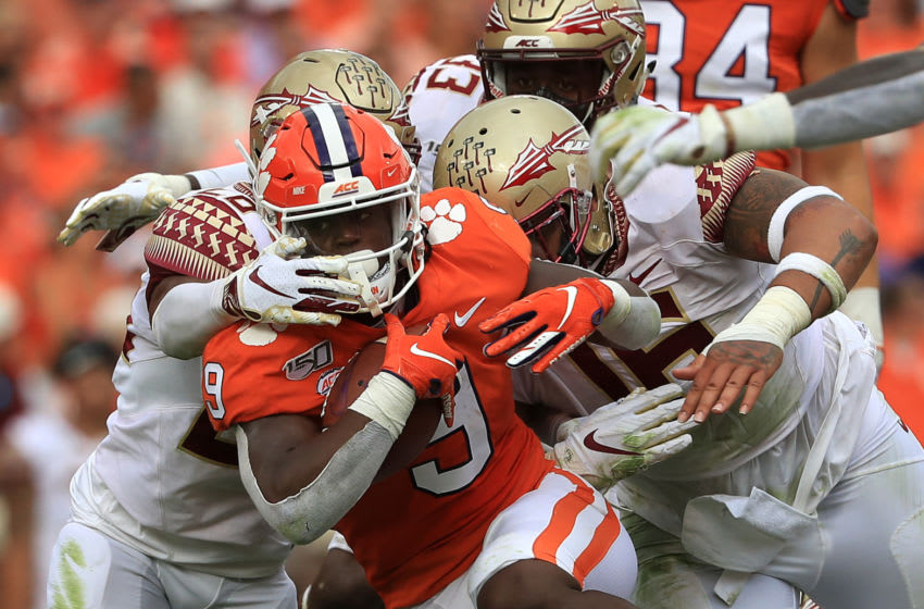CLEMSON, SOUTH CAROLINA - OCTOBER 12: Teammates Cory Durden #16 and Keyshawn Helton #20 of the Florida State Seminoles try to stop Travis Etienne #9 of the Clemson Tigers during their game at Memorial Stadium on October 12, 2019 in Clemson, South Carolina. (Photo by Streeter Lecka/Getty Images)