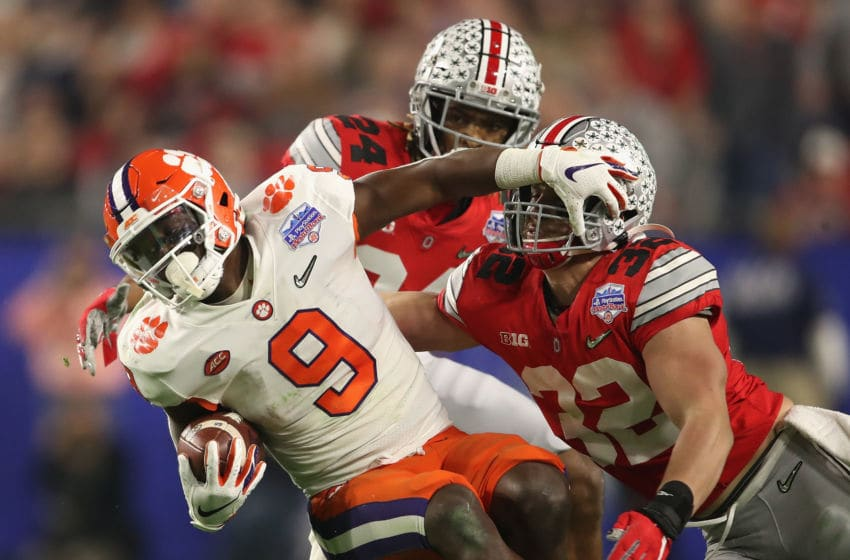 GLENDALE, ARIZONA - DECEMBER 28: Running back Travis Etienne #9 of the Clemson Tigers is tackled by linebacker Tuf Borland #32 of the Ohio State Buckeyes during the PlayStation Fiesta Bowl at State Farm Stadium on December 28, 2019 in Glendale, Arizona. The Tigers defeated the Buckeyes 29-23. (Photo by Christian Petersen/Getty Images)