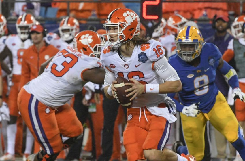 Clemson quarterback Trevor Lawrence (16) rolls out to pass near Pittsburgh linebacker Saleem Brightwell(9) during the second quarter of the Dr. Pepper ACC football championship at Bank of America Stadium in Charlotte, N.C. on Saturday, December 1, 2018. Acc Football Championship Clemson Pitt