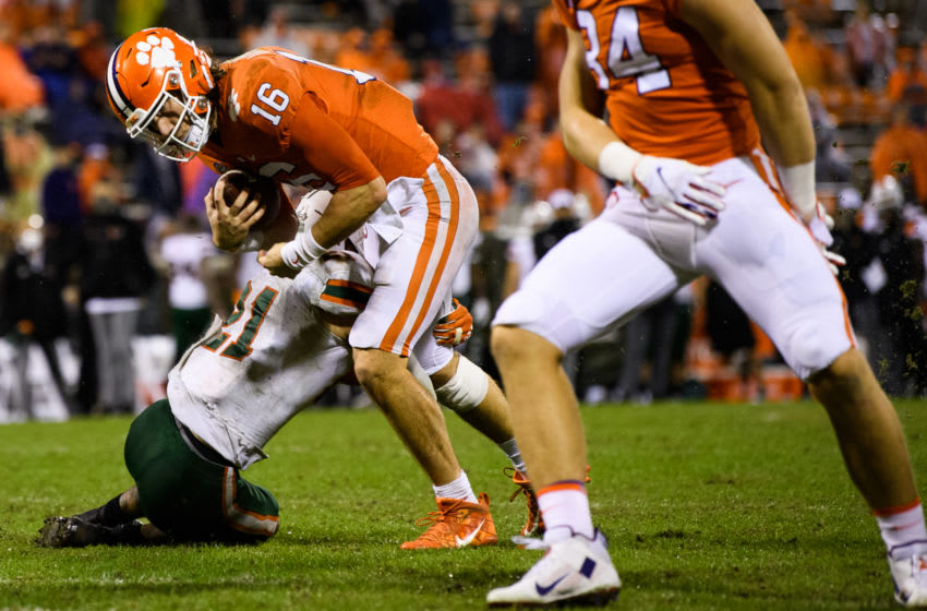 Oct 10, 2020; Clemson, South Carolina, USA; Clemson Tigers quarterback Trevor Lawrence (16) is tackled by Miami Hurricanes safety Bubba Bolden (21) during the third quarter at Memorial Stadium. Mandatory Credit: Ken Ruinard-USA TODAY Sports