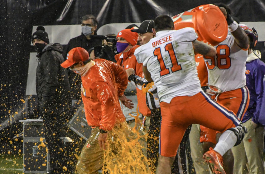 Dec 19, 2020; Charlotte, NC, USA; Clemson head coach Dabo Swinney is dunked with sports drink by freshmen defensive lineman Bryan Bresee (11) and defensive end Myles Murphy (98) during the fourth quarter of the ACC Championship game against Notre Dame at Bank of America Stadium. Mandatory Credit: Ken Ruinard-USA TODAY Sports