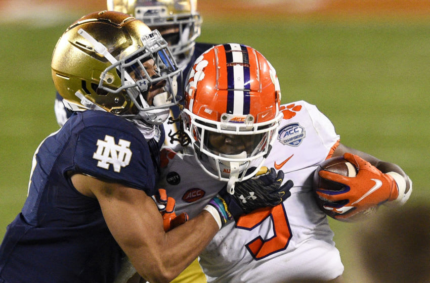 Dec 19, 2020; Charlotte, NC, USA; Clemson Tigers running back Travis Etienne (9) is tackled by Notre Dame Fighting Irish cornerback Nick McCloud (4) in the third quarter at Bank of America Stadium. Mandatory Credit: Bob Donnan-USA TODAY Sports