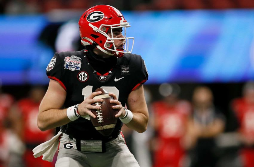 Georgia Bulldogs quarterback JT Daniels (18) drops back to throw a pass in the fourth quarter of the Chick-fil-a Peach Bowl at Mercedes-Benz Stadium in Atlanta on Friday, Jan. 1, 2021. A last-minute field goal sealed a 24-21 win for the Bulldogs, leaving the Bearcats 9-1 on the season. Cincinnati Bearcats Vs Georgia Bulldogs Peach Bowl