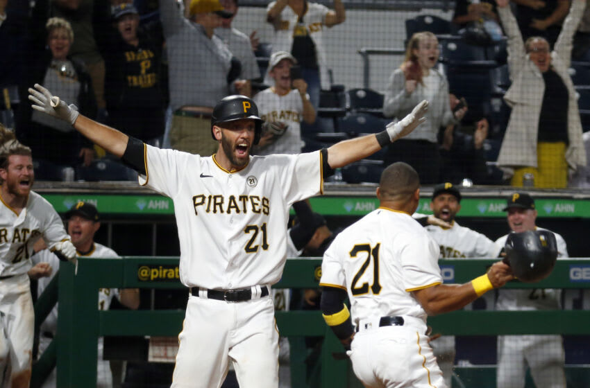 PITTSBURGH, PA - SEPTEMBER 15: Jacob Stallings #58 celebrates with Wilmer Difo #15 of the Pittsburgh Pirates after sliding in safe against Tucker Barnhart #16 of the Cincinnati Reds in the ninth inning to win the game 5-4 during the game at PNC Park on September 15, 2021 in Pittsburgh, Pennsylvania. Puerto Rican MLB players and staff are being given the option of wearing #21 in honor of Roberto Clemente Day. (Photo by Justin K. Aller/Getty Images)