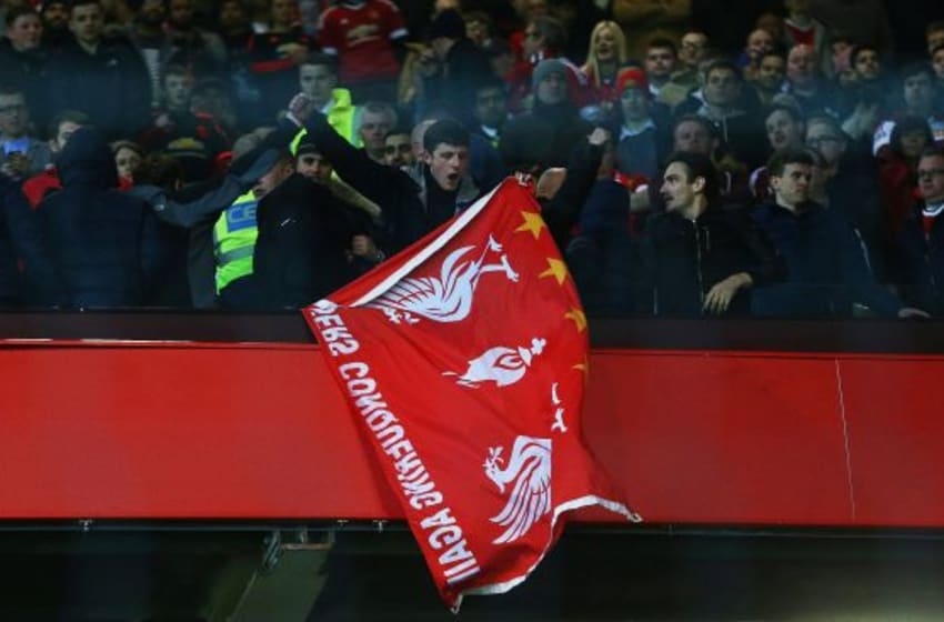 MANCHESTER, ENGLAND - MARCH 17: A Liverpool fan holds a flag as he stands amongst Manchester United supporters after the UEFA Europa League round of 16, second leg match between Manchester United and Liverpool at Old Trafford on March 17, 2016 in Manchester, England. (Photo by Clive Brunskill/Getty Images)