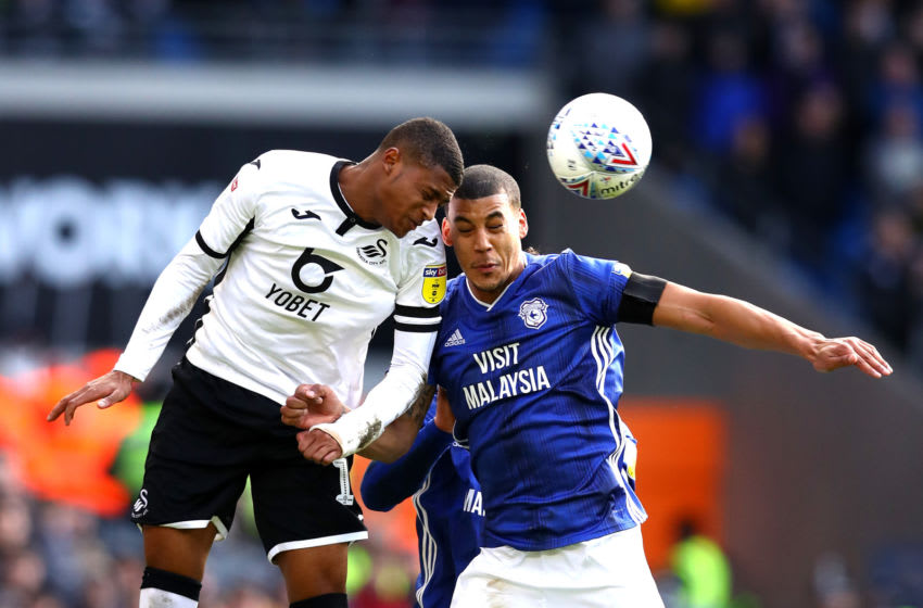 CARDIFF, WALES - JANUARY 12: Lee Peltier of Cardiff City and Rhian Brewster of Swansea City battle for possession during the Sky Bet Championship match between Cardiff City and Swansea City at Cardiff City Stadium on January 12, 2020 in Cardiff, Wales. (Photo by Michael Steele/Getty Images)