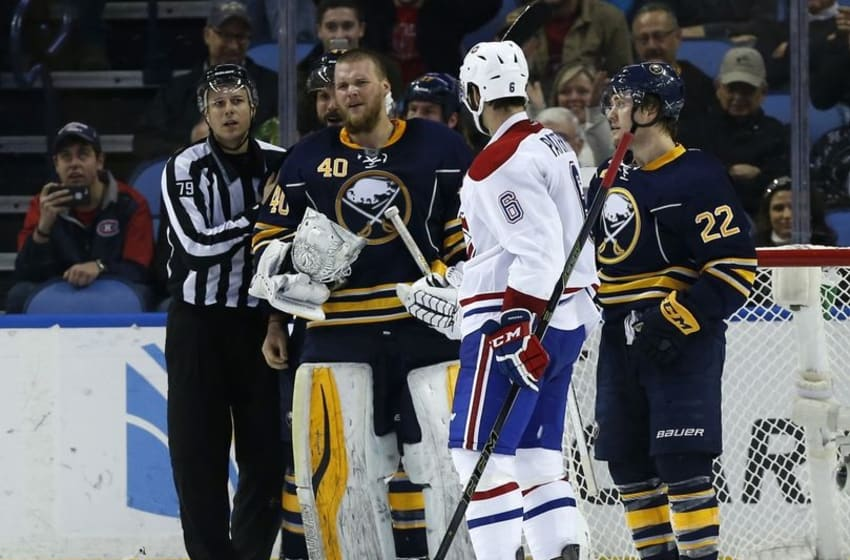 Mar 16, 2016; Buffalo, NY, USA; Buffalo Sabres goalie Robin Lehner (40) is held back by linesman Kiel Murchison (79) as Montreal Canadiens defenseman Greg Pateryn (6) and left wing Johan Larsson (22) looks on after a large scuffle during the second period at First Niagara Center. Mandatory Credit: Kevin Hoffman-USA TODAY Sports