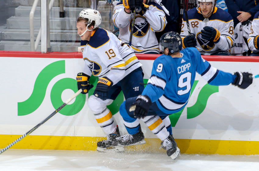 WINNIPEG, MB - NOVEMBER 16: Andrew Copp #9 of the Winnipeg Jets falls to the ice after colliding along the boards with Jake McCabe #19 of the Buffalo Sabres during third period action at the Bell MTS Place on November 16, 2018 in Winnipeg, Manitoba, Canada. (Photo by Jonathan Kozub/NHLI via Getty Images)