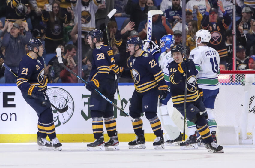 BUFFALO, NY - JANUARY 11: Zemgus Girgensons #28 of the Buffalo Sabres celebrates his game tying goal with Kyle Okposo #21, Johan Larsson #22, and Henri Jokiharju #10. Girgensons goal tied the game at 3-3 with 17:32 remaining in the 3rd period of play the NHL hockey game between the Vancouver Canucks and Buffalo Sabres at KeyBank Center on January 11, 2020 in Buffalo, New York. (Photo by Nicholas T. LoVerde/Getty Images)