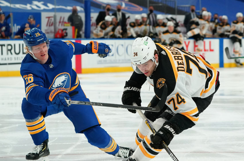 BUFFALO, NY - MARCH 18: Rasmus Dahlin #26 of the Buffalo Sabres defends against Jake DeBrusk #74 of the Boston Bruins during the third period at KeyBank Center on March 18, 2021 in Buffalo, New York. (Photo by Kevin Hoffman/Getty Images)