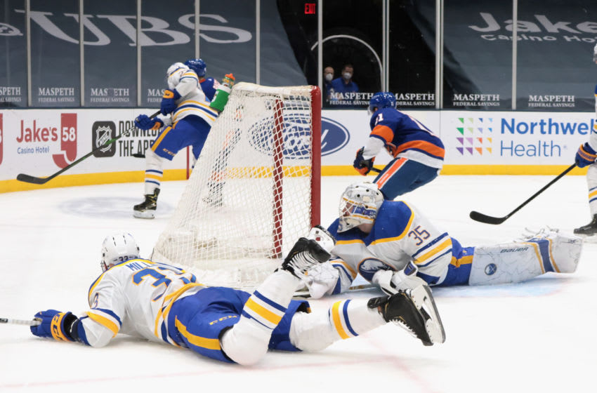 UNIONDALE, NEW YORK - FEBRUARY 22: Colin Miller #33 and Linus Ullmark #35 of the Buffalo Sabres block the net during the second period against the New York Islanders at the Nassau Coliseum on February 22, 2021 in Uniondale, New York. (Photo by Bruce Bennett/Getty Images)