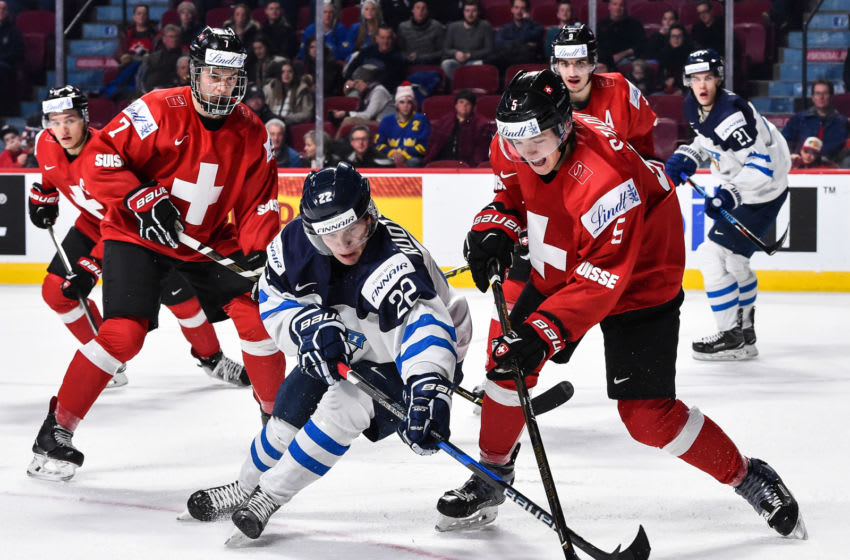 MONTREAL, QC - DECEMBER 31: Arttu Ruotsalainen #22 of Team Finland and Livio Stadler #5 of Team Switzerland chase the puck during the 2017 IIHF World Junior Championship preliminary round game at the Bell Centre on December 31, 2016 in Montreal, Quebec, Canada. (Photo by Minas Panagiotakis/Getty Images)