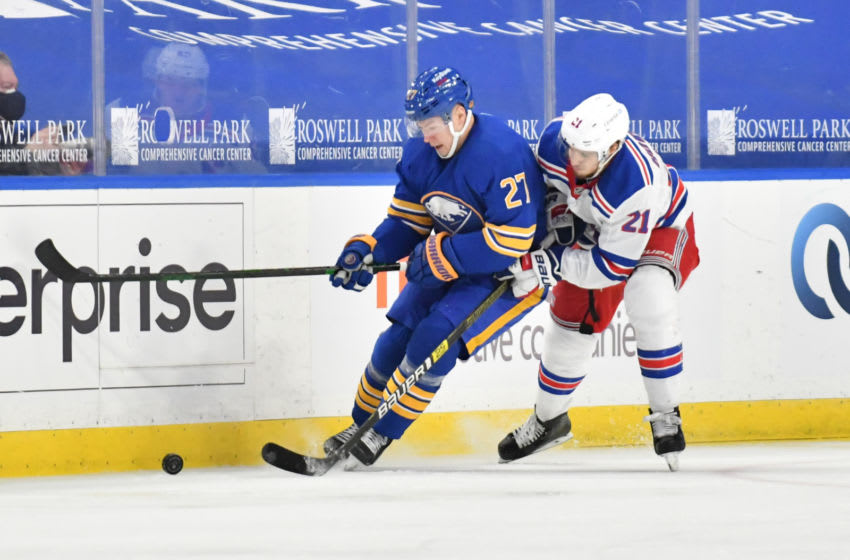 Jan 26, 2021; Buffalo, New York, USA; Buffalo Sabres center Curtis Lazar (27) tries to keep the puck from New York Rangers center Brett Howden (21) in the third period at KeyBank Center. Mandatory Credit: Mark Konezny-USA TODAY Sports