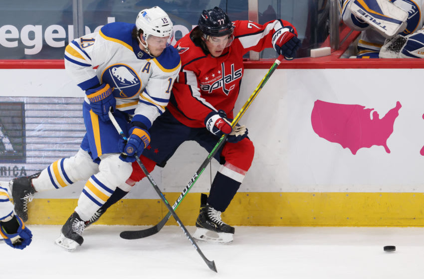 Feb 18, 2021; Washington, District of Columbia, USA; Buffalo Sabres defenseman Jake McCabe (19) and Washington Capitals right wing T.J. Oshie (77) battle for the puck in the first period at Capital One Arena. Mandatory Credit: Geoff Burke-USA TODAY Sports