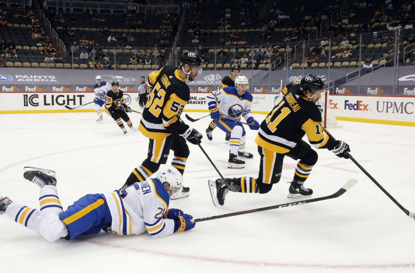May 6, 2021; Pittsburgh, Pennsylvania, USA; Pittsburgh Penguins center Frederick Gaudreau (11) clears the puck against Buffalo Sabres center Arttu Ruotsalainen (25) during the second period at PPG Paints Arena. Mandatory Credit: Charles LeClaire-USA TODAY Sports