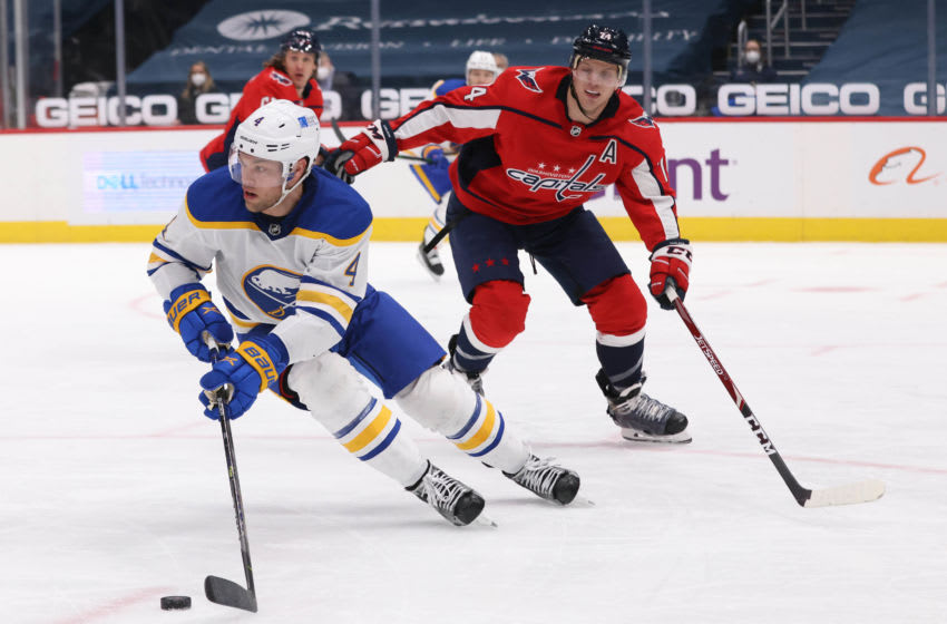 Feb 18, 2021; Washington, District of Columbia, USA; Buffalo Sabres left wing Taylor Hall (4) skates with the puck as Washington Capitals defenseman John Carlson (74) defends in the third period at Capital One Arena. Mandatory Credit: Geoff Burke-USA TODAY Sports