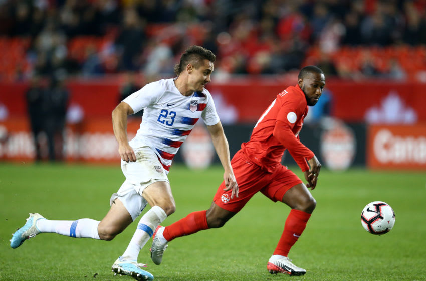 TORONTO, ON - OCTOBER 15: Aaron Long #23 of the United States battles for the ball with David Junior Hoilett #10 of Canada during a CONCACAF Nations League game at BMO Field on October 15, 2019 in Toronto, Canada. (Photo by Vaughn Ridley/Getty Images)