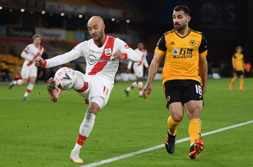 Southampton's English midfielder Nathan Redmond (L) vies with Wolverhampton Wanderers' Spanish defender Jonny Otto (R) during the English FA Cup fifth round football match between Wolverhampton Wanderers and Southampton at the Molineux stadium in Wolverhampton, central England on February 11, 2021. (Photo by Shaun Botterill / POOL / AFP) / RESTRICTED TO EDITORIAL USE. No use with unauthorized audio, video, data, fixture lists, club/league logos or 'live' services. Online in-match use limited to 120 images. An additional 40 images may be used in extra time. No video emulation. Social media in-match use limited to 120 images. An additional 40 images may be used in extra time. No use in betting publications, games or single club/league/player publications. / (Photo by SHAUN BOTTERILL/POOL/AFP via Getty Images)