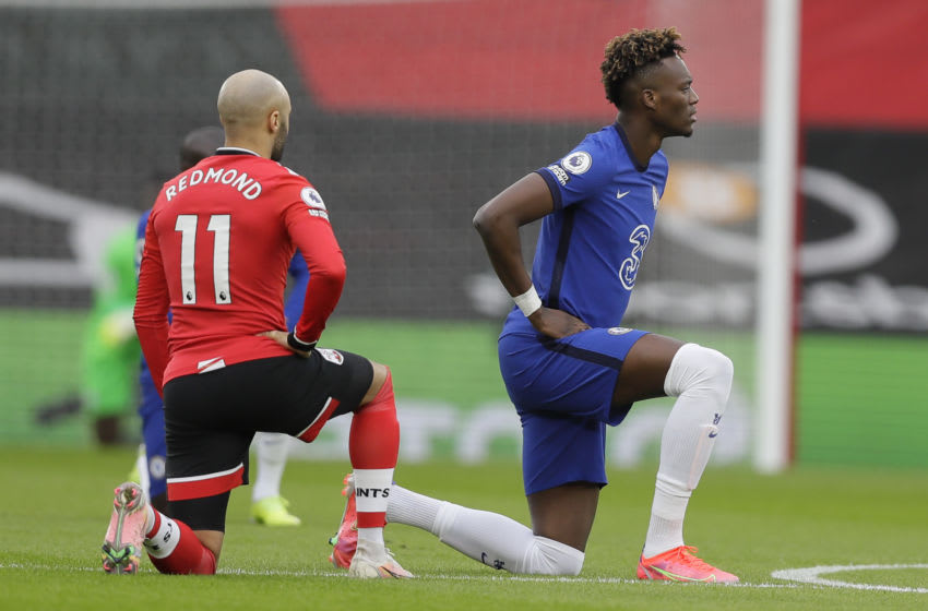 Southampton's English midfielder Nathan Redmond (L) and Chelsea's English striker Tammy Abraham take the knee during the English Premier League football match between Southampton and Chelsea at St Mary's Stadium in Southampton, southern England on February 20, 2021. (Photo by Kirsty Wigglesworth / POOL / AFP) / RESTRICTED TO EDITORIAL USE. No use with unauthorized audio, video, data, fixture lists, club/league logos or 'live' services. Online in-match use limited to 120 images. An additional 40 images may be used in extra time. No video emulation. Social media in-match use limited to 120 images. An additional 40 images may be used in extra time. No use in betting publications, games or single club/league/player publications. / (Photo by KIRSTY WIGGLESWORTH/POOL/AFP via Getty Images)