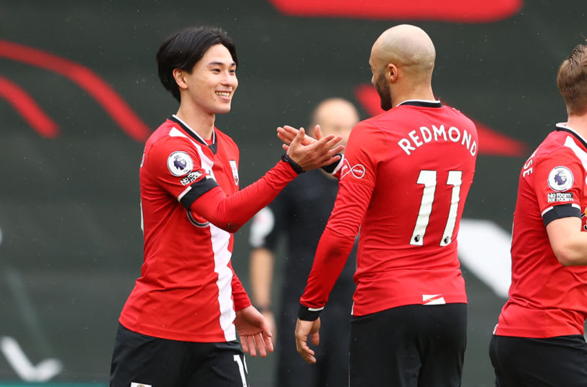 Southampton's Japanese midfielder Takumi Minamino (L) celebrates with Southampton's English midfielder Nathan Redmond (R) after scoring the opening goal of the English Premier League football match between Southampton and Chelsea at St Mary's Stadium in Southampton, southern England on February 20, 2021. (Photo by MICHAEL STEELE / POOL / AFP) / RESTRICTED TO EDITORIAL USE. No use with unauthorized audio, video, data, fixture lists, club/league logos or 'live' services. Online in-match use limited to 120 images. An additional 40 images may be used in extra time. No video emulation. Social media in-match use limited to 120 images. An additional 40 images may be used in extra time. No use in betting publications, games or single club/league/player publications. / (Photo by MICHAEL STEELE/POOL/AFP via Getty Images)