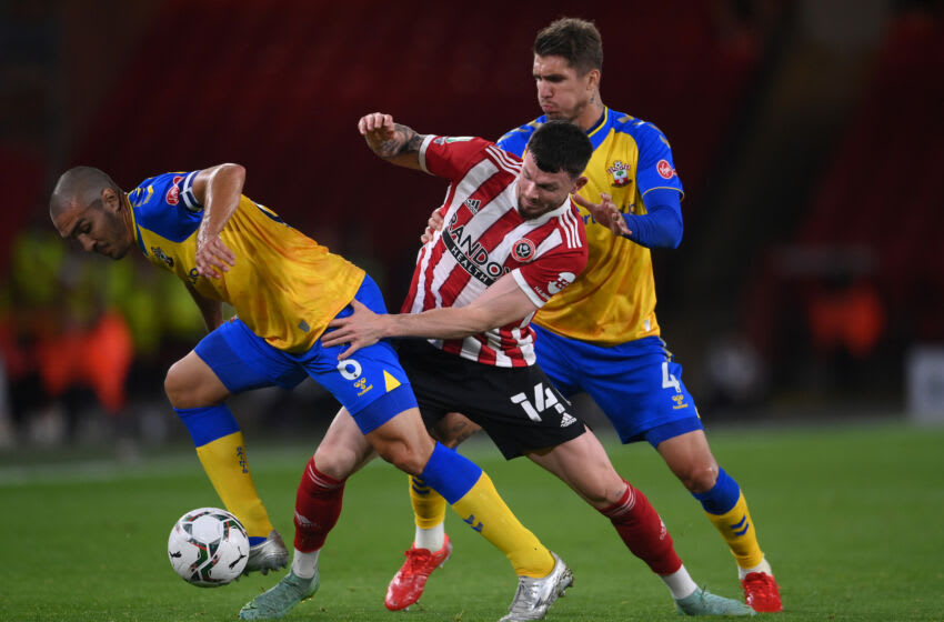 SHEFFIELD, ENGLAND - SEPTEMBER 21: Oliver Burke of Sheffield United is tackled by Oriol Romeu of Southampton (L) and Lyanco of Southampton (R) during the Carabao Cup Third Round match between Sheffield United and Southampton at Bramall Lane on September 21, 2021 in Sheffield, England. (Photo by Laurence Griffiths/Getty Images)