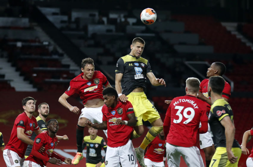 Southampton's Polish defender Jan Bednarek (C) wins a header in the build-up to their late equalizer during the English Premier League football match between Manchester United and Southampton at Old Trafford in Manchester, north-west England, on July 13, 2020. - The game finished 2-2. (Photo by Clive Brunskill / POOL / AFP) / RESTRICTED TO EDITORIAL USE. No use with unauthorized audio, video, data, fixture lists, club/league logos or 'live' services. Online in-match use limited to 120 images. An additional 40 images may be used in extra time. No video emulation. Social media in-match use limited to 120 images. An additional 40 images may be used in extra time. No use in betting publications, games or single club/league/player publications. / (Photo by CLIVE BRUNSKILL/POOL/AFP via Getty Images)