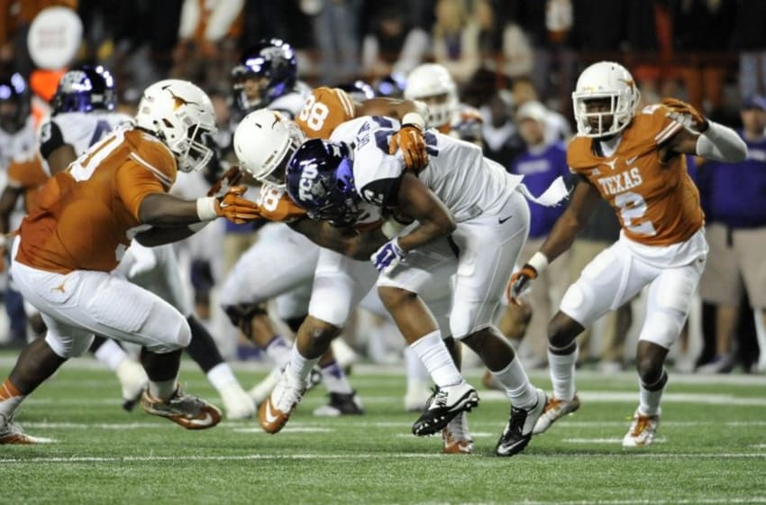 Nov 27, 2014; Austin, TX, USA; TCU Horned Frogs running back Aaron Green (22) is tackled by Texas Longhorns defensive end Cedric Reed (88) and defensive tackle Malcom Brown (90) during the game at Darrell K Royal-Texas Memorial Stadium. Mandatory Credit: Brendan Maloney-USA TODAY Sports