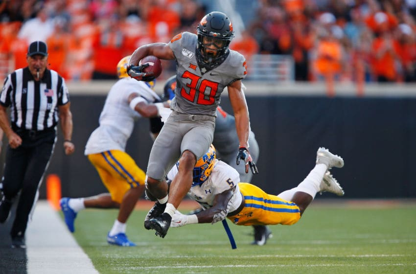 STILLWATER, OK - SEPTEMBER 7: Running back Chuba Hubbard #30 of the Oklahoma State Cowboys leaps to escape the reach of defensive back Jovon Burriss #5 of the McNeese State Cowboys in the second quarter on September 7, 2019 at Boone Pickens Stadium in Stillwater, Oklahoma. (Photo by Brian Bahr/Getty Images)