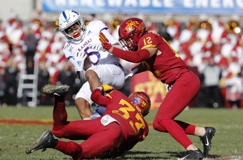 AMES, IA - NOVEMBER 23: \Wide receiver Stephon Robinson Jr. #5 of the Kansas Jayhawks is tackled by defensive back Braxton Lewis #33 of the Iowa State Cyclones, and defensive back Greg Eisworth #12 of the Iowa State Cyclones as he rushed for yards in the first half of play at Jack Trice Stadium on November 23, 2019 in Ames, Iowa. (Photo by David Purdy/Getty Images)