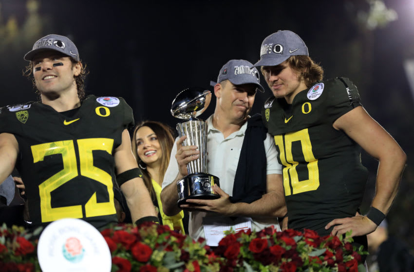 PASADENA, CALIFORNIA - JANUARY 01: Head coach Mario Cristobal (C), Brady Breeze (L) #25 and Justin Herbert (R) #10 of the Oregon Ducks celebrate after defeating the Wisconsin Badgers in the Rose Bowl game presented by Northwestern Mutual at Rose Bowl on January 01, 2020 in Pasadena, California. (Photo by Sean M. Haffey/Getty Images)