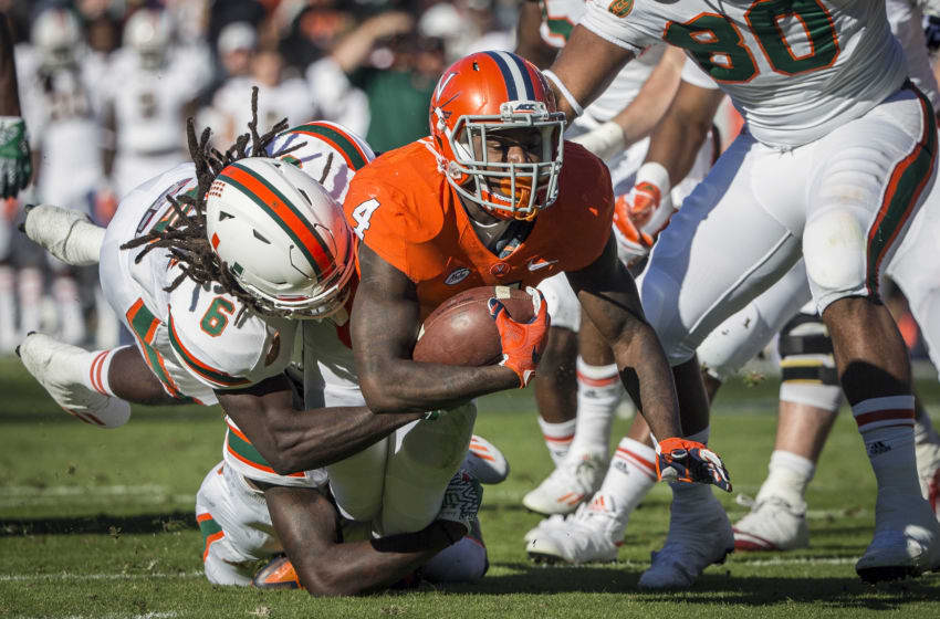 CHARLOTTESVILLE, VA - NOVEMBER 12: Taquan Mizzell #4 of the Virginia Cavaliers is brought down by Jamal Carter Sr. #6 of the Miami Hurricanes during a game at Scott Stadium on November 12, 2016 in Charlottesville, Virginia. (Photo by Chet Strange/Getty Images)