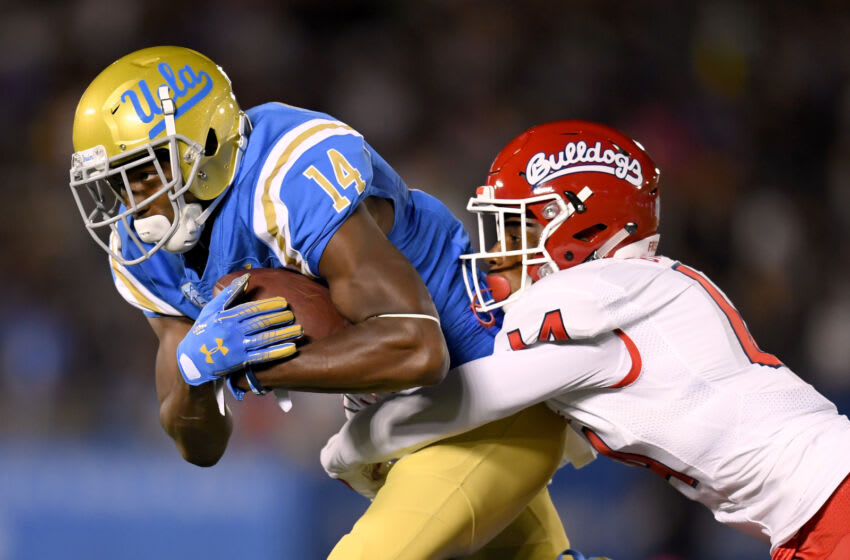 PASADENA, CA - SEPTEMBER 15: Theo Howard #14 of the UCLA Bruins is tackled by Jaron Bryant #14 of the Fresno State Bulldogs during the second quarter at Rose Bowl on September 15, 2018 in Pasadena, California. (Photo by Harry How/Getty Images)