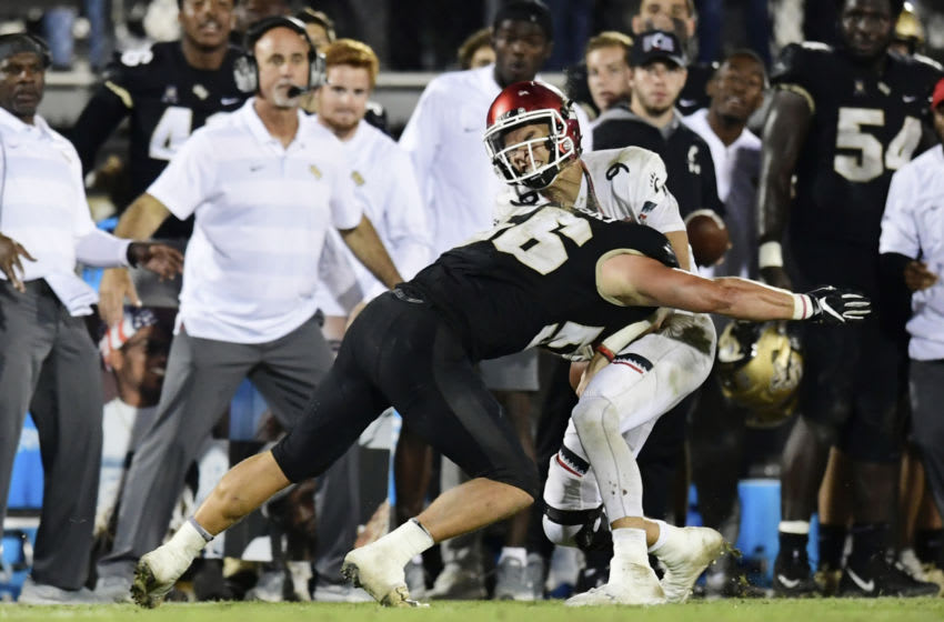 ORLANDO, FLORIDA - NOVEMBER 17: Pat Jasinski #56 of the UCF Knights knocks the ball loose from Desmond Ridder #9 of the Cincinnati Bearcats during the third quarter on November 17, 2018 at Spectrum Stadium in Orlando, Florida. (Photo by Julio Aguilar/Getty Images)