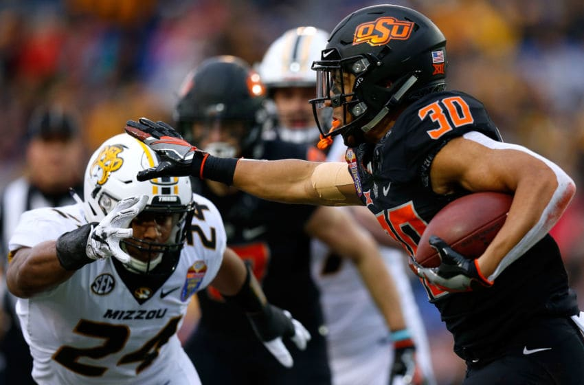 MEMPHIS, TENNESSEE - DECEMBER 31: Chuba Hubbard #30 of the Oklahoma State Cowboys runs with the ball as Terez Hall #24 of the Missouri Tigers defends during the first half of the AutoZone Liberty Bowl at Liberty Bowl Memorial Stadium on December 31, 2018 in Memphis, Tennessee. (Photo by Jonathan Bachman/Getty Images)