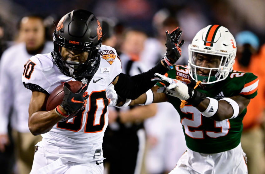 Dec 29, 2020; Orlando, FL, USA; Oklahoma State Cowboys wide receiver Brennan Presley (80) makes a reception as Miami Hurricanes cornerback Te'Cory Couch (23) defends during the first half of the Cheez-It Bowl Game at Camping World Stadium. Mandatory Credit: Douglas DeFelice-USA TODAY Sports