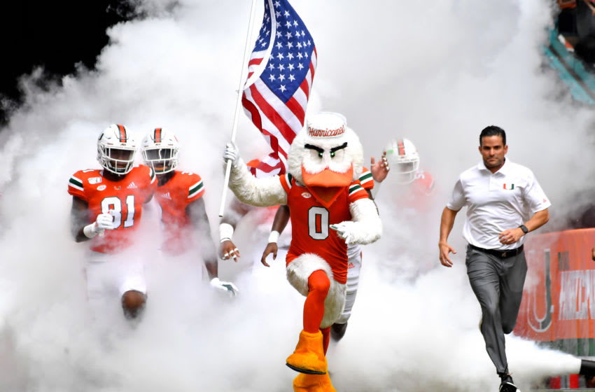 Oct 19, 2019; Miami Gardens, FL, USA; Miami Hurricanes mascot Sebastian (left) runs out with head coach Manny Diaz (right) before a game against the Georgia Tech Yellow Jackets at Hard Rock Stadium. Mandatory Credit: Steve Mitchell-USA TODAY Sports
