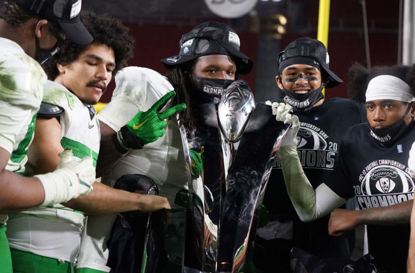 Dec 18, 2020; Los Angeles, California, USA; Oregon Ducks players pose with trophy after the Pac-12 Championship against the Southern California Trojans at United Airlines Field at Los Angeles Memorial Coliseum. Oregon defeated USC 31-24. Mandatory Credit: Kirby Lee-USA TODAY Sports