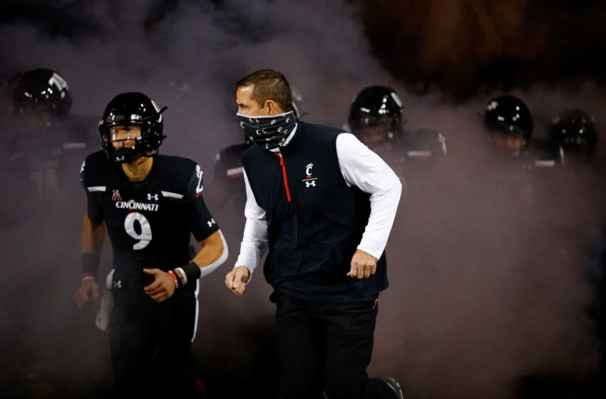 Cincinnati Bearcats head coach Luke Fickell and quarterback Desmond Ridder (9) lead the Bearcats onto the field before the first quarter of the NCAA American Athletic Conference football game between the Cincinnati Bearcats and the East Carolina Pirates at Nippert Stadium in Cincinnati on Friday, Nov. 13, 2020. The Bearcats led 35-10 at halftime. East Carolina Pirates At Cincinnati Bearcats