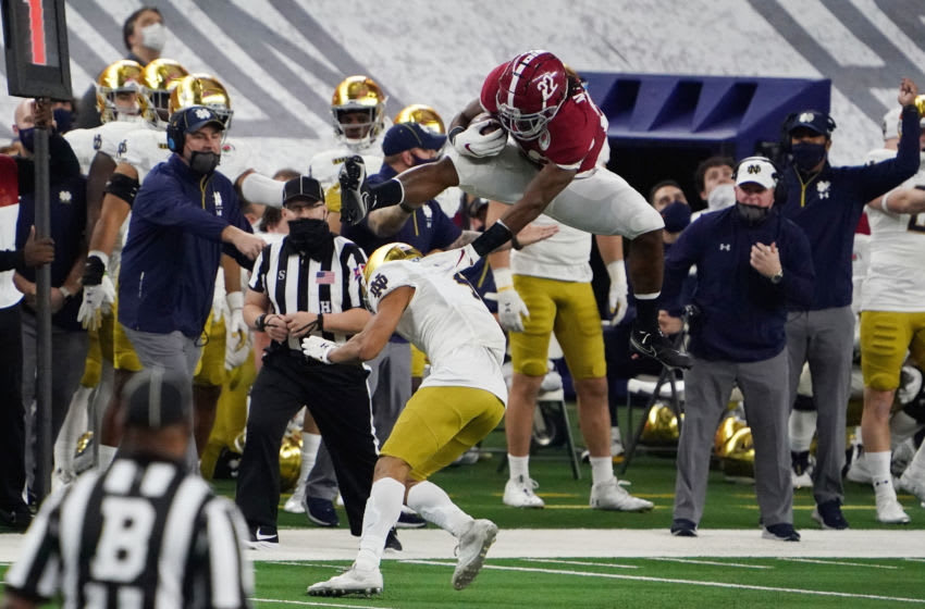 Jan 1, 2021; Arlington, TX, USA; Alabama Crimson Tide running back Najee Harris (22) jumps over Notre Dame Fighting Irish cornerback Nick McCloud (4)during the Rose Bowl at AT&T Stadium. Mandatory Credit: Kirby Lee-USA TODAY Sports