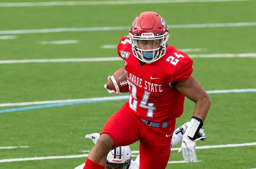 Delaware State University's Wade Inge (24) breaks a tackle while running the ball in the first quarter against MEAC rival Howard University in the Hornets' 17-10 win in their season and home opener Saturday, Feb. 27, 2021. Wil Delstate Football