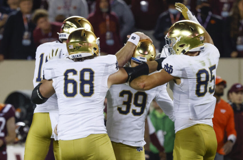 Oct 9, 2021; Blacksburg, Virginia, USA; Notre Dame Fighting Irish place kicker Jonathan Doerer (39) celebrates with offensive lineman Michael Carmody (68) and tight end George Takacs (85) after he makes the game winning field goal from the hold of punter Jay Bramblett (left) against the Virginia Tech Hokies at Lane Stadium. Mandatory Credit: Reinhold Matay-USA TODAY Sports