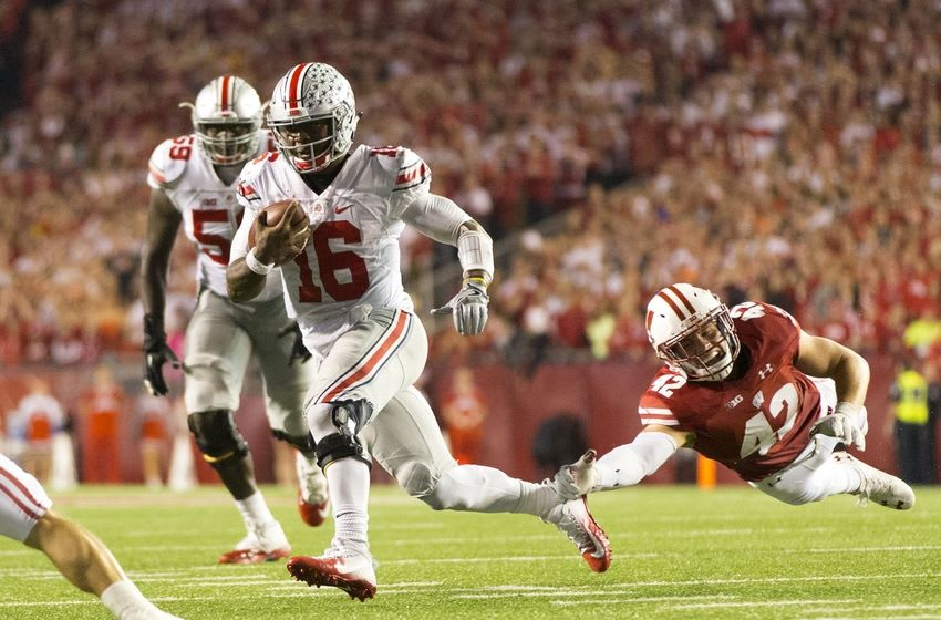 Oct 15, 2016; Madison, WI, USA; Ohio State Buckeyes quarterback J.T. Barrett (16) rushes with the football as Wisconsin Badgers linebacker T.J. Watt (42) dives from behind during the fourth quarter at Camp Randall Stadium. Ohio State won 30-23. Mandatory Credit: Jeff Hanisch-USA TODAY Sports