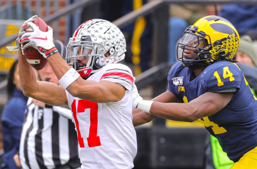 ANN ARBOR, MI - NOVEMBER 30: Chris Olave #17 of the Ohio State Buckeyes makes a touchdown catch as Josh Metellus #14 of the Michigan Wolverines gives chase during the first quarter of the game at Michigan Stadium on November 30, 2019 in Ann Arbor, Michigan. Ohio State defeated Michigan 56-27. (Photo by Leon Halip/Getty Images)