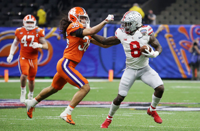 NEW ORLEANS, LOUISIANA - JANUARY 01: Trey Sermon #8 of the Ohio State Buckeyes stiff arms Lannden Zanders #36 of the Clemson Tigers in the first half during the College Football Playoff semifinal game at the Allstate Sugar Bowl at Mercedes-Benz Superdome on January 01, 2021 in New Orleans, Louisiana. (Photo by Chris Graythen/Getty Images)