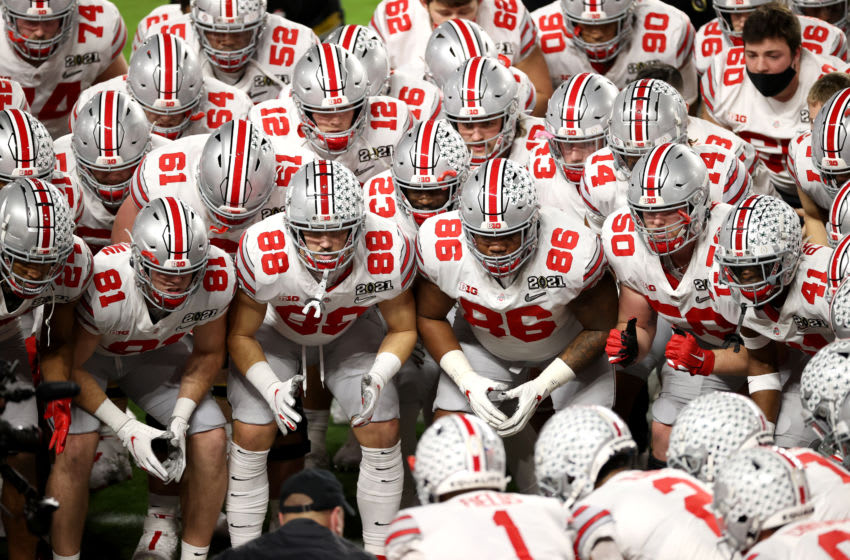 MIAMI GARDENS, FLORIDA - JANUARY 11: Jeremy Ruckert #88 and Chris Booker #86 of the Ohio State Buckeyes huddle with their teammates before the College Football Playoff National Championship against the Alabama Crimson Tide at Hard Rock Stadium on January 11, 2021 in Miami Gardens, Florida. (Photo by Jamie Schwaberow/Getty Images)